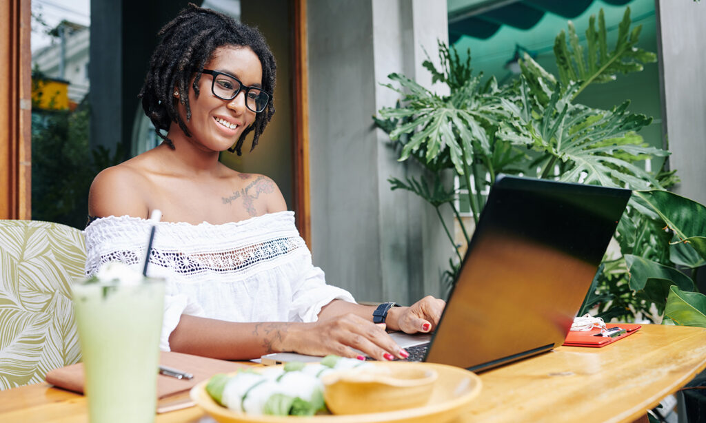 beautiful African American woman smiling while she types on her laptop